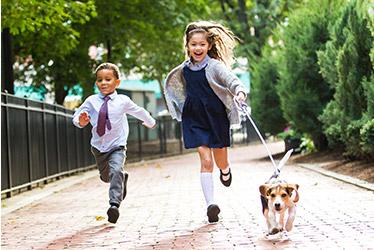 Smiling kids wearing school uniform running on the sidewalk.