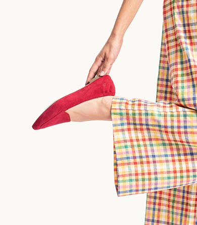 Person with rainbow colored pants wearing red Hush Puppies Hazel Pointe shoes.