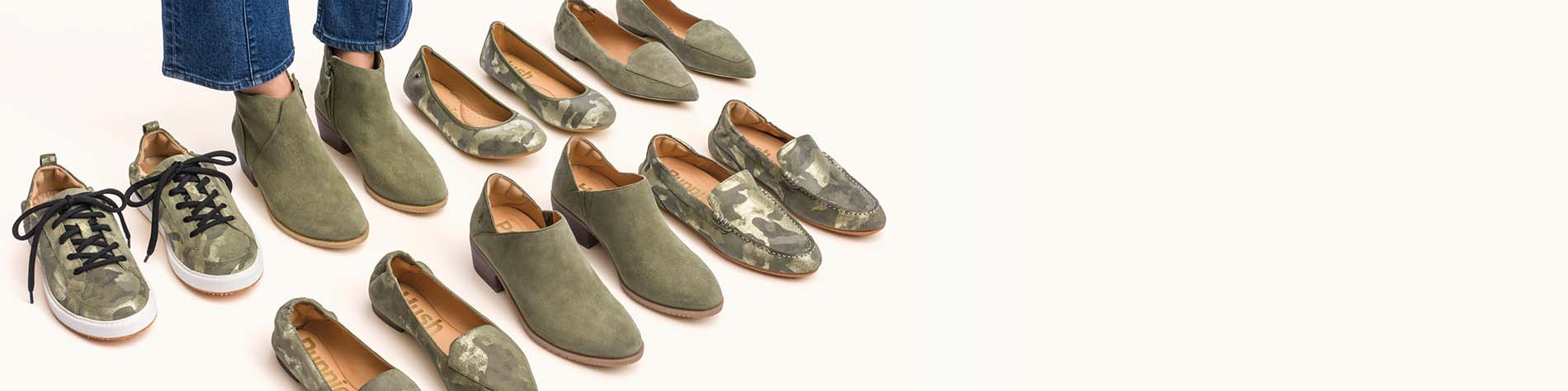 A pair of feet in a pair of olive shoes, hiding in a selction of other olive and camo colored shoes.