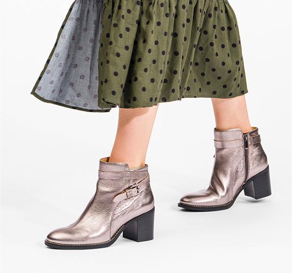 Woman in a green polk-a-dot skirt wearing Hannah Strap Boots in Gunmetal Metallic Leather