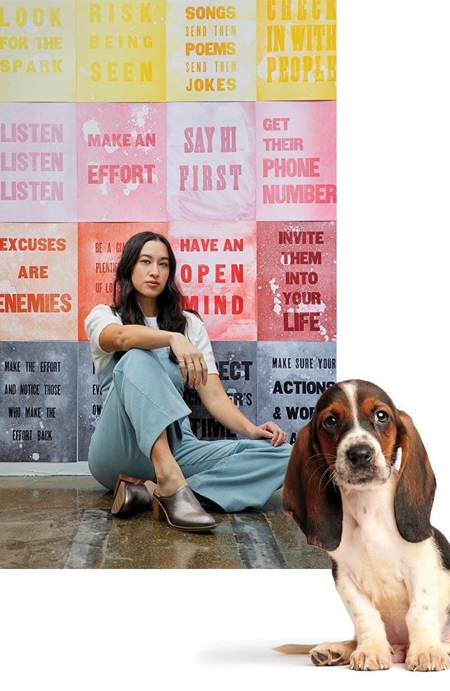 A Basset Hound puppy adorably looking back at you. Female sitting in front of an inspirational wall of signs.