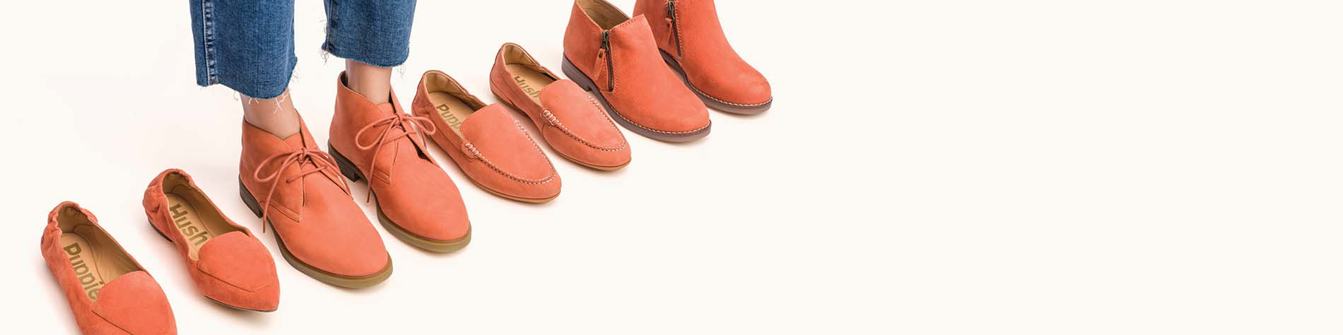 A pair of feet in a pair of ginger shoes, in line with a selction of other ginger shoes.