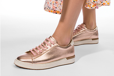 Gold sneakers with white soles and pink laces.