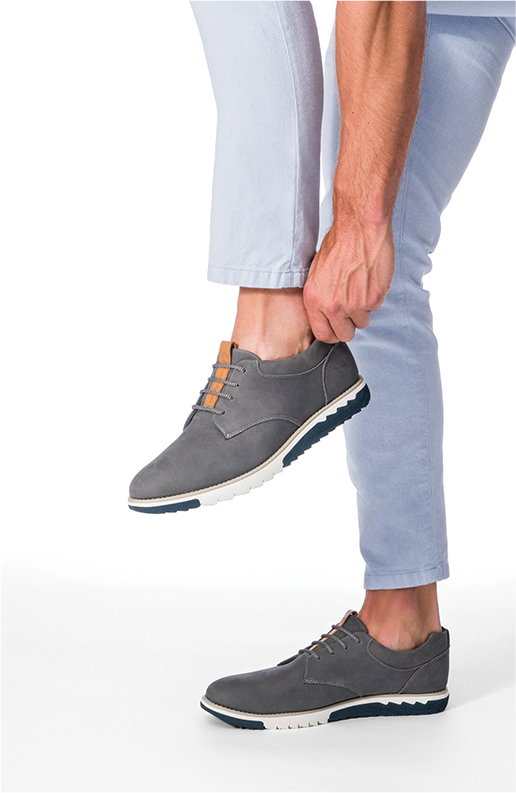 A man putting on his grey oxford sneaker.