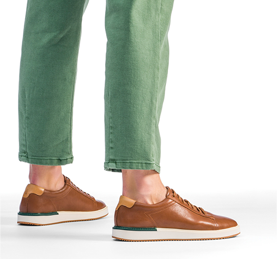Man in green jeans wearing a pair of heath sneakers.